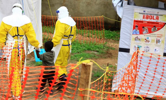 Health workers walk with a boy suspected as having the Ebola virus at an Ebola treatment centre in Beni, Eastern Congo, on Sept. 9, 2018.  (Al-hadji Kudra Maliro/AP)