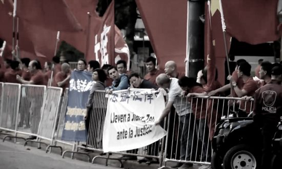 """Nine Argentine Falun Gong practitioners hang two banners on the crowd control barriers, which say """"Stop the persecution of Falun Gong"""" and """"Bring Jiang Zemin to Justice"""" in Spanish and Chinese. The practitioners are surrounded by supporters of the Chinese Communist Party sent to welcome Chinese leader Xi Jinping. (Screenshot via YouTube)"""