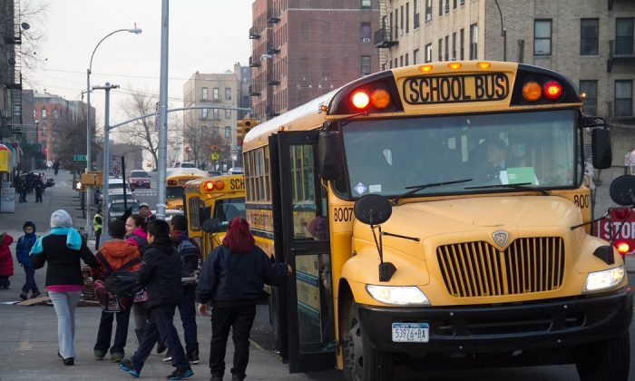Students exit a school bus in front of their school in the Bronx, New York City, on Jan. 9, 2013. (Benjamin Chasteen/The Epoch Times)