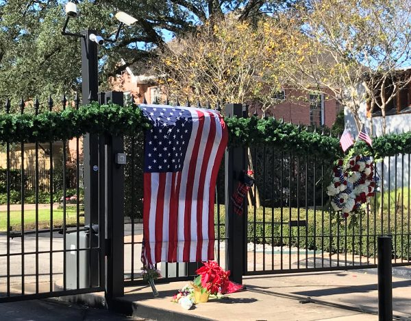 A flag is draped over the gate to the neighborhood of the home of former President George H.W. Bush