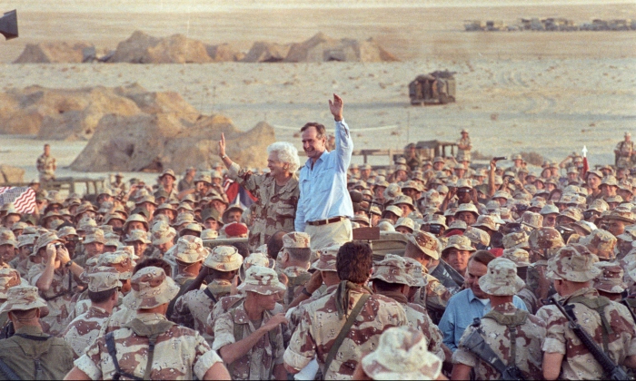 President George H. W. Bush waves goodbye to U.S. Marines and members of the British 7th Armoured Brigade as they conclude a Thanksgiving Day visit with troops in the Saudi desert on Nov. 22, 1990. (Rick Wilking/Reuters)