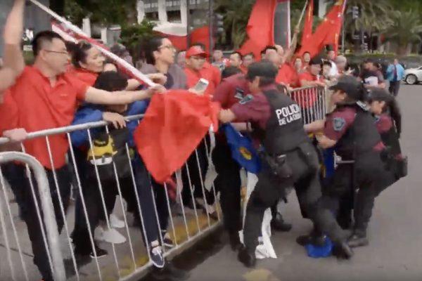 Um participante do grupo pró-Pequim ataca um praticante do Falun Gong com um mastro de bandeira (Captura de tela via YouTube)