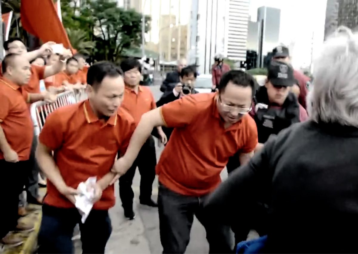 Os partidários do Partido Comunista Chinês pegam e agitam os panfletos que estavam dentro de uma bolsa de um praticante do Falun Gong que caiu no chão em 29 de novembro em Buenos Aires, Argentina (Screenshot / via YouTube)