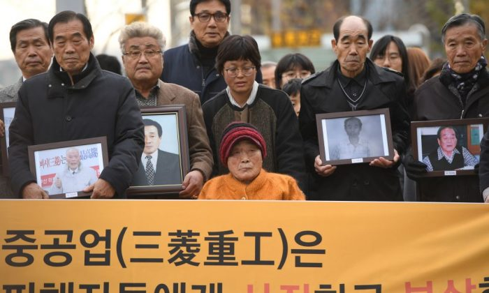 Kim Sung-joo (bottom C), a victim of forced labor by Japan during its colonial rule of the Korean peninsula from 1910 to 1945, and relatives of other victims arrive at the Supreme Court in Seoul on Nov. 29, 2018. South Korea's top court on Nov. 29 ordered a Japanese heavy industries giant to pay compensation over forced wartime labor, despite a previous 1965 settlement. (JUNG YEON-JE/AFP/Getty Images)