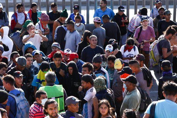 Migrantes voltam para o acampamento depois de uma tentativa fracassada de invadir a fronteira dos EUA e entrar ilegalmente, a oeste da travessia de San Ysidro, em Tijuana, México, em 25 de novembro de 2018. A cerca no fundo não é a fronteira, é uma cerca secundária no lado do México (Charlotte Cuthbertson / The Epoch Times)