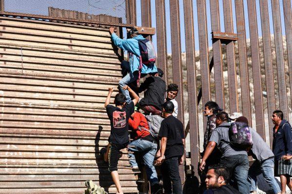 Migrantes atravessam a cerca da fronteira dos Estados Unidos logo depois da entrada leste de pedestre da travessia de San Ysidro, em Tijuana, México, em 25 de novembro de 2018 (Charlotte Cuthbertson / The Epoch Times)