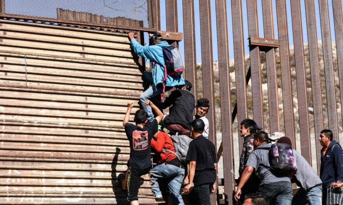 Migrants break through the U.S. border fence just beyond the east pedestrian entrance of the San Ysidro crossing in Tijuana, Mexico, on Nov. 25, 2018. (Charlotte Cuthbertson/The Epoch Times)