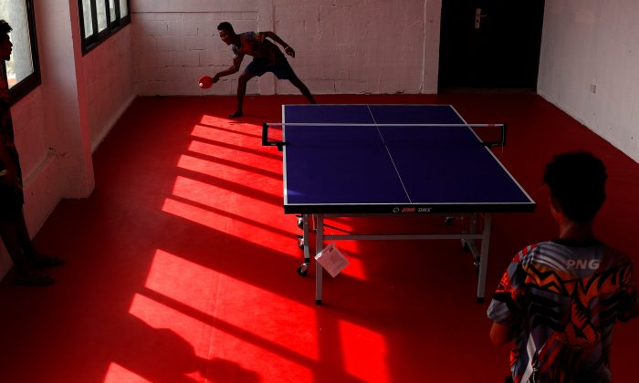 Papua New Guinea table tennis players Goada Elly and David Thomas play on a table during a practice session at a Beijing-funded facility in central Port Moresby, Papua New Guinea on Nov. 19, 2018. (David Gray/Reuters)