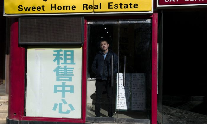 A real estate agent waits for customers inside his office in Beijing on January 17, 2016. (FRED DUFOUR/AFP/Getty Images)