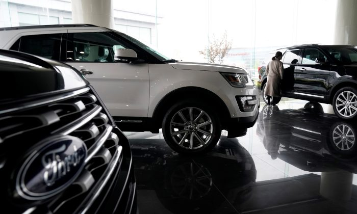 A woman looks at Ford cars at a dealer shop in Shanghai, China on April 5, 2018. (Aly Song/Reuters)