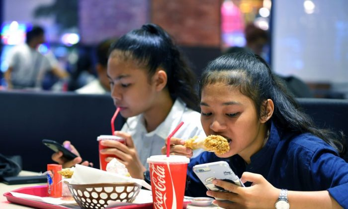 Cambodian teenagers use phones while eating at a restaurant in Phnom Penh on Oct. 28, 2018. (Tang Chhin Sothy/AFP/Getty Images)