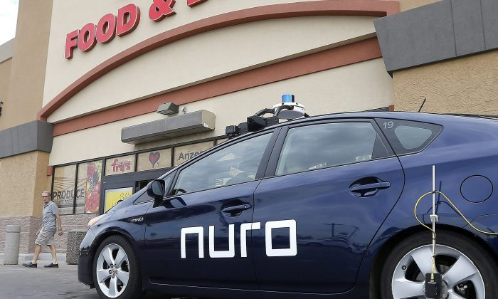 A self-driving Nuro vehicle is parked outside a supermarket in Scottsdale, Arizona, as part of a pilot program using driverless cars to deliver groceries, Aug. 16, 2018. (AP Photo/Ross D. Franklin)