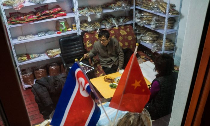 In this photograph taken on January 8, 2018, a North Korean seafood seller eats dinner at his shop with his wife in the border city of Dandong, in China's northeast Liaoning province. (CHANDAN KHANNA/AFP/Getty Images)