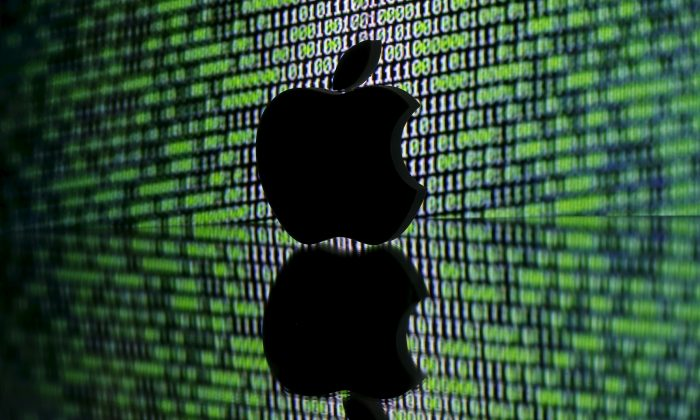 A 3D printed Apple logo is seen in front of a displayed cyber code in this illustration taken Mar. 22, 2016. (Dado Ruvic/Illustration/Reuters)