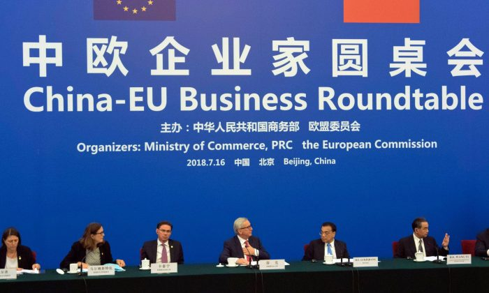 China's Premier Li Keqiang (2nd R) looks over to European Commission President Jean-Claude Juncker (C) as they attend the China-EU Business Roundtable at the Great Hall of the People in Beijing on July 16, 2018. (Ng Han Guan /AFP/Getty Images)