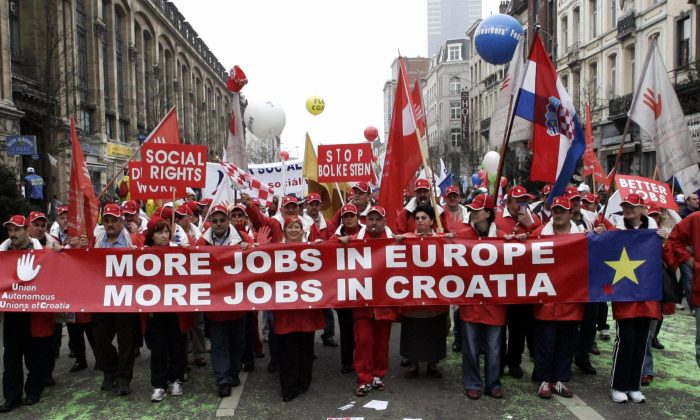 Unfolding a large banner calling for more jobs in Europe and in Croatia a group of protesters as part of some 50,000 people coming from Belgium, Germany, France, The Netherlands, Poland and others, demonstrate 19 March 2005 in the streets of Brussels in a anti-EU Neo liberal policies demonstration organized by European Trade Unions. (Gerard Cerles/AFP/Getty Images)