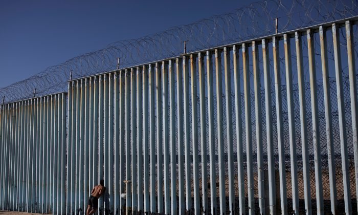 A migrant from Honduras looks through the border wall on the beach of Tijuana, Mexico, on Dec. 3, 2018. (Alkis Konstantinidis/Reuters)