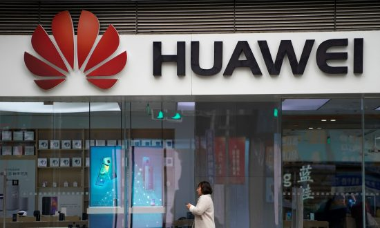 A woman walks by a Huawei logo at a shopping mall in Shanghai, China on Dec. 6, 2018. (Aly Song/Reuters)