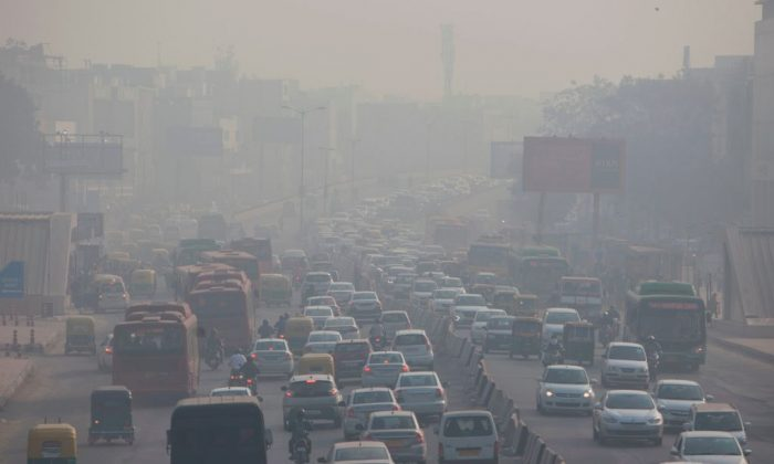 Indian commuters drive amidst heavy smog along a busy road past the South Extension area of New Delhi on Dec. 6, 2018. (Xavier Galiana/AFP/Getty Images)