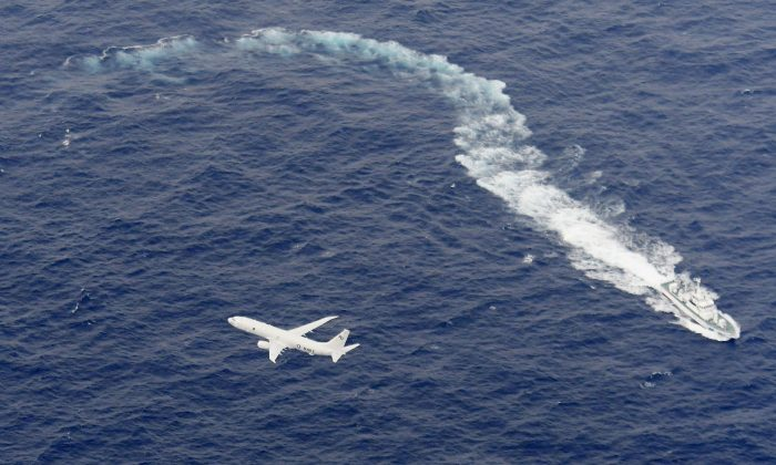A Japan Coast Guard patrol vessel and U.S. Navy airplane conduct search and rescue operation at the area where two U.S. Marine Corps aircraft have been involved in a mishap in the skies, off the coast of Kochi prefecture, Japan, in this aerial view photo taken by Kyodo on Dec. 6, 2018.  (Mandatory credit Kyodo/via Reuters)