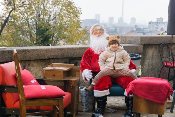 Child sits on fake Santa lap in front of view of Zagreb
