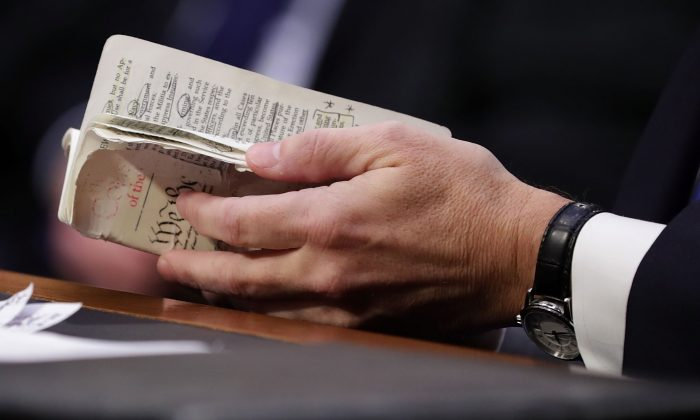 Supreme Court Justice Brett Kavanaugh thumbs through a well-worn, pocket-sized copy of the U.S. Constitution as he testifies before the Senate Judiciary Committee on the second day of his confirmation hearing on Capitol Hill, Sept. 5, 2018, in Washington, DC. (Chip Somodevilla/Getty Images)