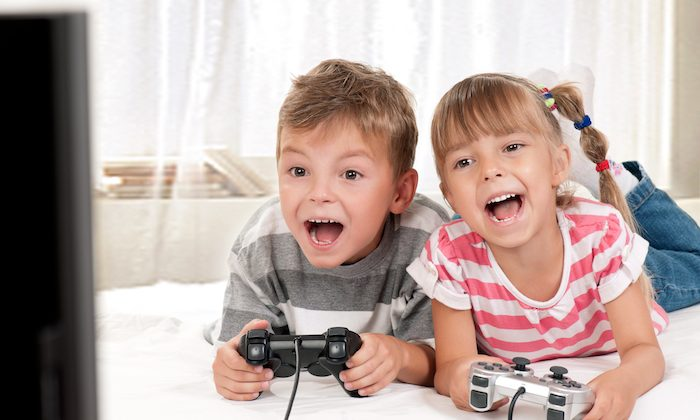 Happy children - girl and boy playing a video game. (Shutterstock)