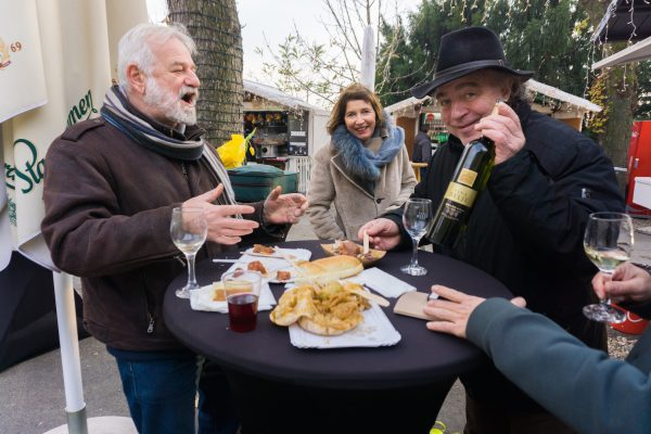 Men and women laugh and eat Croatian Christmas market food and wine in Zagreb