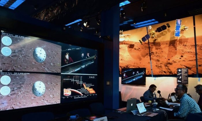 People watch the landing of NASA's InSight spacecraft on the planet Mars on television screens at NASA's Jet Propulsion Laboratory in Pasadena, Calif., on Nov. 26, 2018. (Frederic J. Brown/AFP/Getty Images)