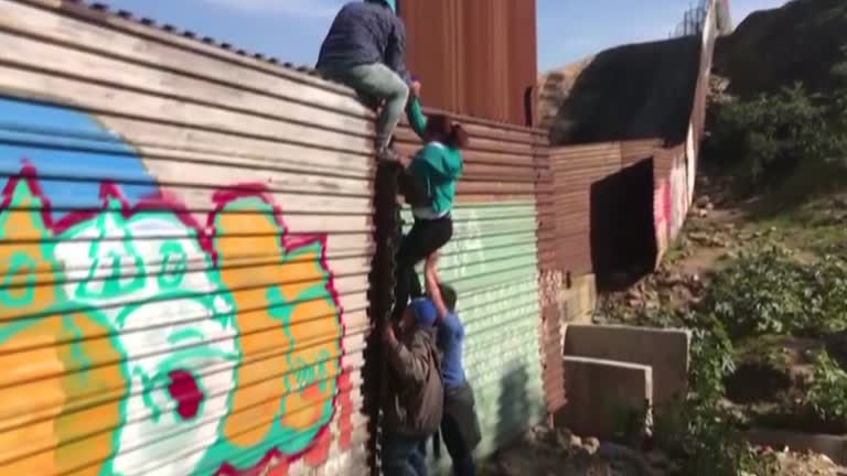 migrants climb fence in daylight