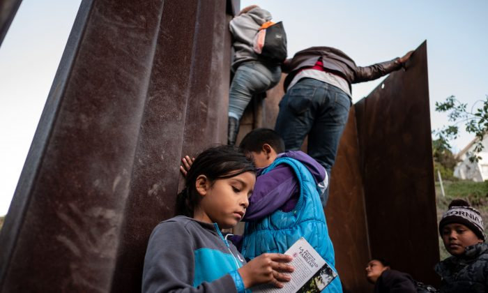 A Central American migrant girl holds a book as other migrants travelling in a caravan, climb the Mexico-US border fence in an attempt to cross to San Diego County, in Playas de Tijuana, Baja California state, Mexico on Dec. 12, 2018. (Guillermo Arias/AFP/Getty Images)