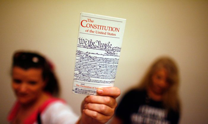 "In this file photo, a woman holds up a copy of the U.S. Constitution at the Rayburn House Office Building on Capitol Hill, Washington, DC. There is a growing call for a ""convention of states"" to propose new constitutional amendments to address term limits on Congress and the Supreme Court, trim federal power, and require Congress to exercise more fiscal restraint. (Chip Somodevilla/Getty Images)"