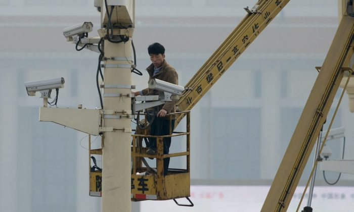 File photo showing a man checking security cameras at Tiananmen Square in Beijing, Oct. 31, 2013. (Ed Jones/Getty Images/AFP)