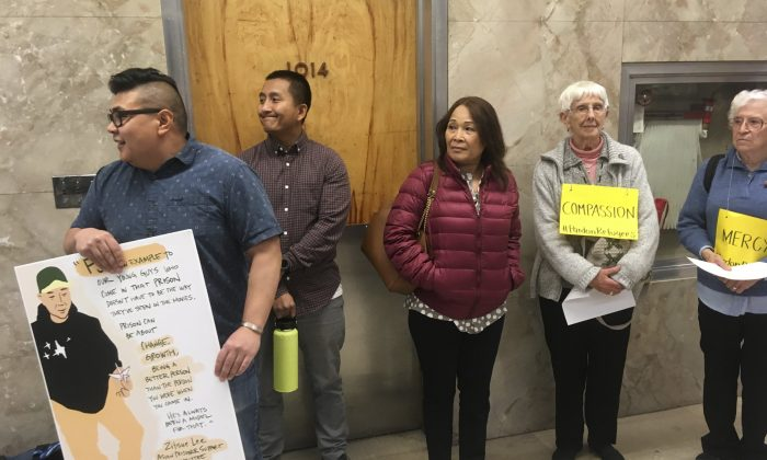 """Andrew Medina, left, holds a sign during a rally backing a pardon for Borey Ai, who also goes by """"PJ"""" or """"Peejay,"""" in Sacramento, Calif., on Oct. 24, 2018. (Don Thompson/AP)"""