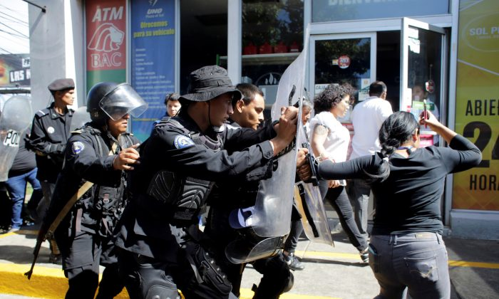 Riot police dislodge journalists from the main entrance to the police headquarters in Managua, Nicaragua, on Dec. 15, 2018. (Reuters/Oswaldo Rivas)
