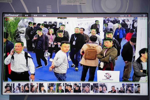 A screen shows visitors being filmed by artificial intelligence security cameras