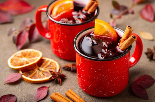 Two cups of autumn mulled wine or gluhwein with spices and orange slices on rustic table top view. Traditional drink on autumn holiday on the background of autumn leaves - Image. (Shutterstock)