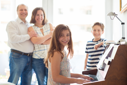 Happy young family listening how children plays piano music at home. (Shutterstock)