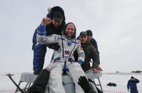 Ground personnel help International Space Station crew member Alexander Gerst of Germany to get out of the Soyuz MS-09 capsule