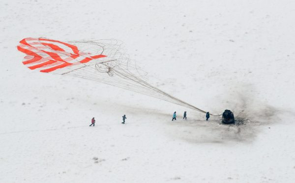 A search and rescue team approaches the Soyuz MS-09 capsule