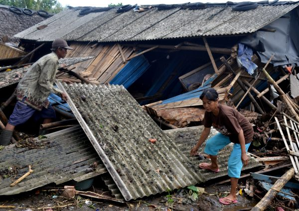 residents collect debris after tsunami