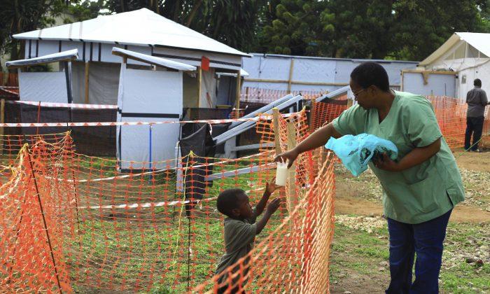 A health worker passes a drink to a boy suspecting of having the Ebola virus at an Ebola treatment center in Beni, Eastern Congo, on Sept 9, 2018. (AP Photo/Al-hadji Kudra Maliro)