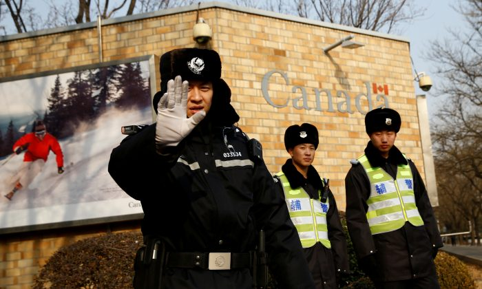 A police officer gestures at the photographer as security staff stand guard outside the Canadian embassy in Beijing, China, on Dec. 20, 2018.  (Thomas Peter/Reuters)