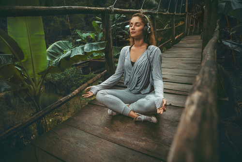 Young beautiful yoga woman listen to the music on suspension bridge in the tropic forest - Image