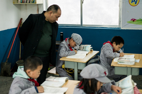 """This photo taken on November 7, 2016 shows a teacher supervising students in the Yang Dezhi """"Red Army"""" elementary school in Wenshui, Xishui country in Guizhou province.  In 2008, Yang Dezhi was designated a """"Red Army primary school"""" -funded by China's """"red nobility"""" of revolution-era Communist commanders and their families one of many such institutions that have been established across the country. Such schools are an extreme example of the """"patriotic education"""" which China's ruling Communist party promotes to boost its legitimacy - but which critics condemn as little more than brainwashing. (FRED DUFOUR/AFP/Getty Images)"""