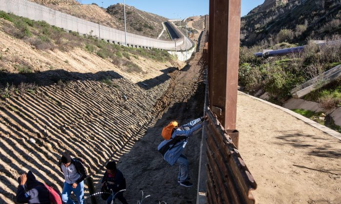 Central American migrants hoping to reach the United States cross the US-Mexico border fence from Tijuana (R), Baja California State, Mexico, to the U.S., on Dec. 30, 2018. (GUILLERMO ARIAS/AFP/Getty Images)