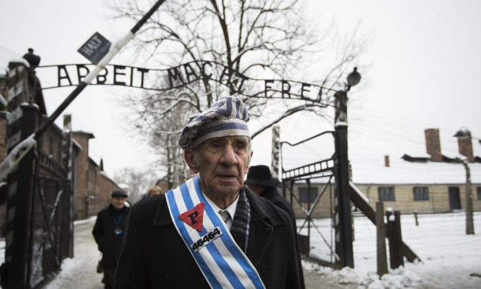 "Auschwitz survivor Miroslaw Celka walks out of the death camp gate with the sign above it saying ""Work makes you free,"" on the 70th anniversary of the liberation of the Nazi extermination facility in southern Poland, on Jan. 27, 2015. (Odd Andersen/AFP/Getty Images)"
