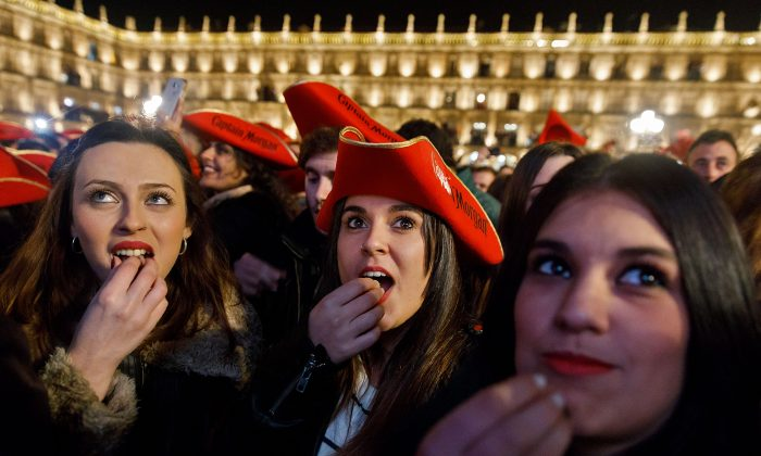 Students eat grape gummies while celebrating the traditional year-end party held in the main square of Salamanca, Spain on Dec. 15, 2016. 