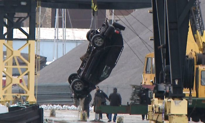 WISN-TV shows authorities pulling out an SUV from the Kinnickinnic River, a day after it crashed into the river during a police chase on Dec. 31, 2018. (WISN-TV/AP)