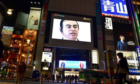 A pedestrian walks past a screen showing a news programme featuring Nissan chairman Carlos Ghosn in Tokyo on Nov. 22, 2018. (Kazuhiro Nogi/AFP/Getty Images)
